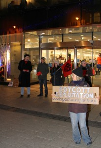 a person holds a placard outside M&S