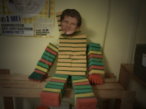 Effigy of the manager of the forced labour centre made out of the sponges that people on workfare are forced to cut